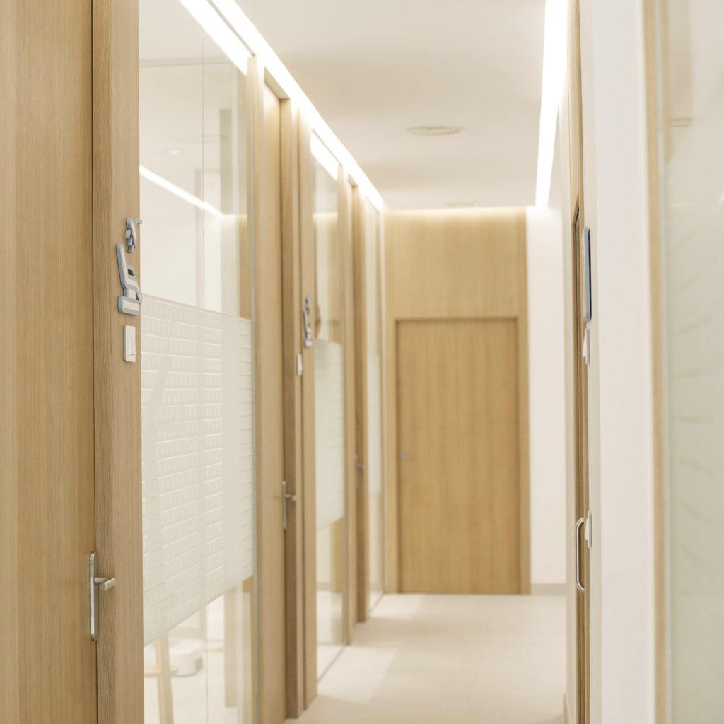 Clínica Dental Acacias. El pasillo, con puertas de madera de roble de acceso a los gabinetes, y grandes ventanales de vidrio. Mecanismos Simon 82 Detail madera natural.